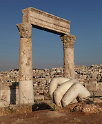 Temple of Hercules, Amman Citadel, Jabal al Qal'a, Amman, Jordan. This Roman temple was built in 162-66 AD and is dedicated to co-emperors Marcus Aurelius & Lucius Verus. Showing 2 columns with corinthian capitals, and in foreground, hand of colossal Roman statue, probably of god Hercules. This fragment belonged to a colossal statue from the Roman period and was found near the Temple. The statue is estimated to have stood over 13 metres high making it one of the largest statues from Greco-Roman times. Due to the massiveness of the statue, the temple was attributed to Hercules who was renowned for his physical strength. Cityscape of downtown Amman visible in the background. Picture by Manuel Cohen