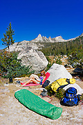Woman relaxing in camp under Echo Peaks (backpacking gear visible), Yosemite National Park, California