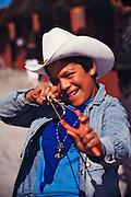 Tarahumara Indian boy jokingly aiming his slingshot at tourists.