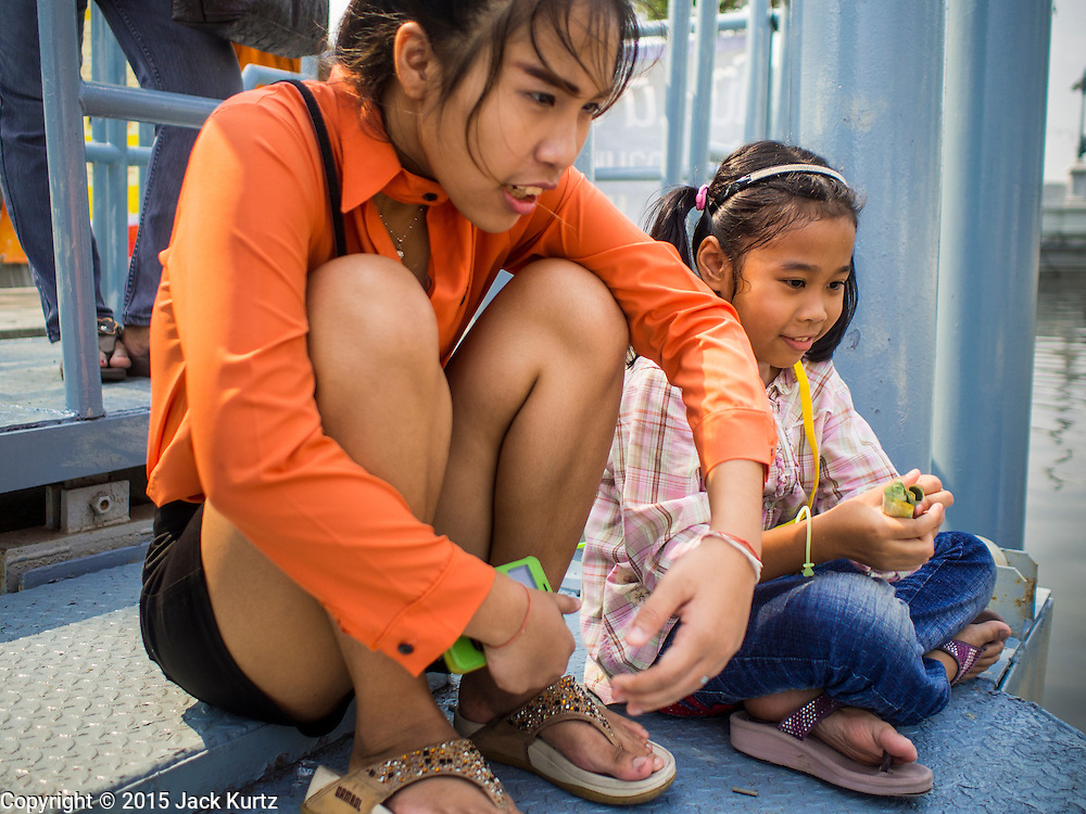 12 FEBRUARY 2015 - BANGKOK, THAILAND: Children on a pier wait for a vendor to cook their noodle orders at the new floating market opened on Khlong Phadung Krung Kasem, a 5.5 kilometre long canal dug as a moat around Bangkok in the 1850s. The floating market opened at the north end of the canal near Government House, which is the office of the Prime Minister. The floating market was the idea of Thai Prime Minister General Prayuth Chan-ocha. The market will be open until March 1.    PHOTO BY JACK KURTZ