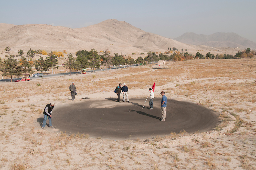 "Golfers enjoy the outdoors and the opportunity to escape the city at the Kabul Golf Club, Kabul, Afghanistan.  The nine hole (18 holes if played in reverse) par 36 course is 5,522 yards of hard packed desert sand, scrub brush, ants, and persistent thorns.  The course has no grass. The greens are ""browns,"" made from sand saturated with motor oil to keep them from blowing away."