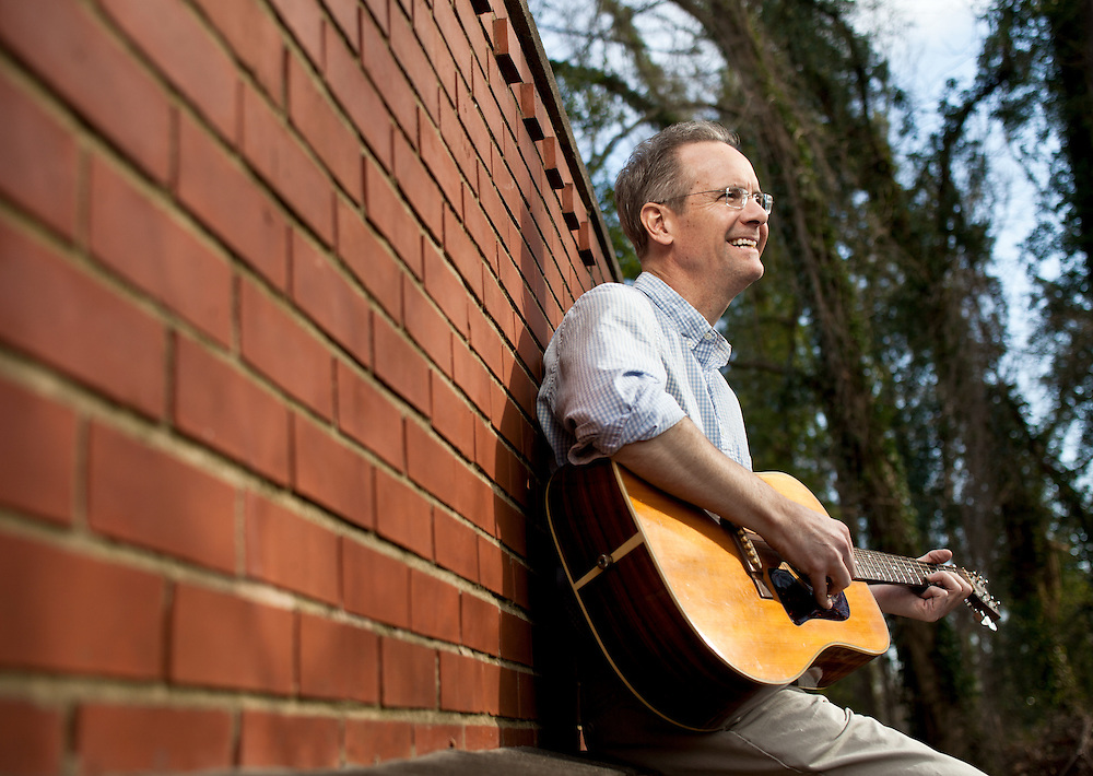 Editorial photo of Haywood Barnes playing his acoustic guitar outdoors. I mage made for a financial publication.