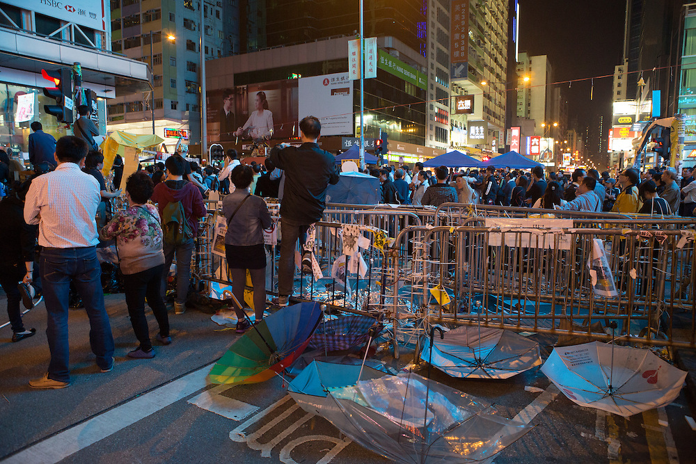 Discarded umbrellas, the symbol of the protest movement, lie behind barricades.