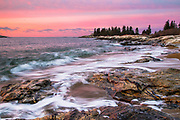 Waves crash at sunrise along the rocky, sandy beach in Reid State Park.