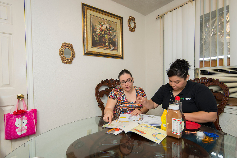 Nelly Salazar, left, gets guidance from Home Instruction for Parents of Pre-K Youth (HIPPY) home instructor Blanca Ramirez, right, March 26, 2014.
