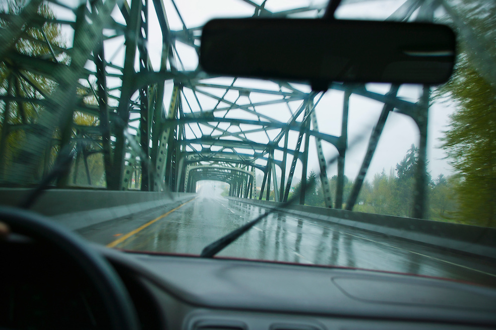 A first person / drivers perspective of driving on a highway across a steel beam bridge in the rain.