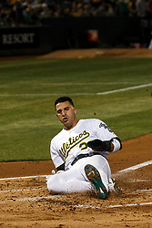 OAKLAND, CA - SEPTEMBER 16: Ramon Laureano #22 of the Oakland Athletics slides into home plate to score a run against the Kansas City Royals during the first inning at the RingCentral Coliseum on September 16, 2019 in Oakland, California. The Kansas City Royals defeated the Oakland Athletics 6-5. (Photo by Jason O. Watson/Getty Images) *** Local Caption *** Ramon Laureano
