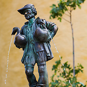 A fountain with a statue of a man holding two swans and the Hohenschwangau Castle in Bavaria, Germany.