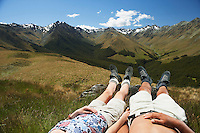 Man and woman laying in grass by mountains low section