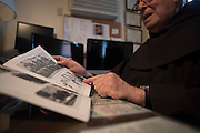 New York, NY, April 2, 2016. Franciscan Brother Paschal DeMattea, O.F.M. looks at photos in the office of St. Anthony of Padua in New York City. 04/02/2016. Photo by George Goss/NYCity News Service.