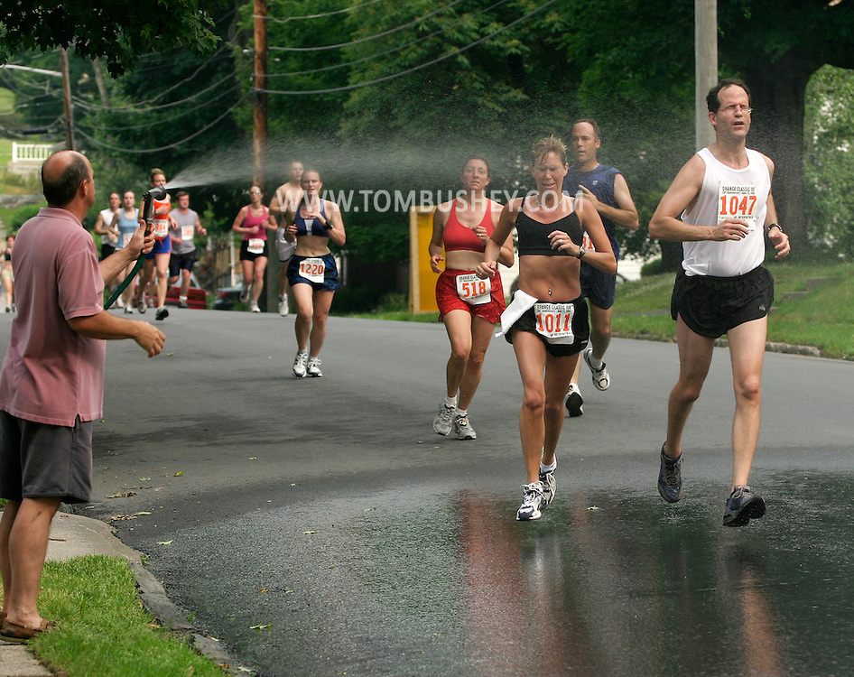 Runners get cooled off in the spray from a spectator's hose during the 25th annual Orange Classic 10K road race in Middletown, N.Y., on June 11, 2005. The weather for the race was hot and humid.