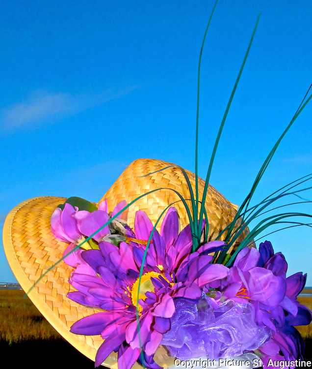 Celebrating spring... a woman wears a straw hat with bright purple flowers.