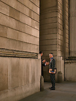 Two businessmen talking at entrance of monumental building