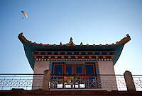 Paraglider soars over a temple in the tibetan colony of Bir, India