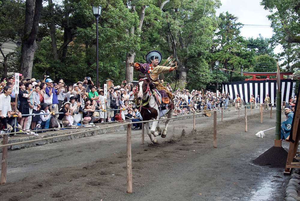 """A participant dressed in traditional attire fires his arrow at a target during the """"yabusame-shinji"""" mounted archery ritual on the 3-day Reitaisai grand festival in Kamakura, Japan on  16 Sept. 2012.  Archers ride at speed and attempt to hit three targets along a 250-meter course erected inside the shrine grounds. Photographer: Robert Gilhooly"""