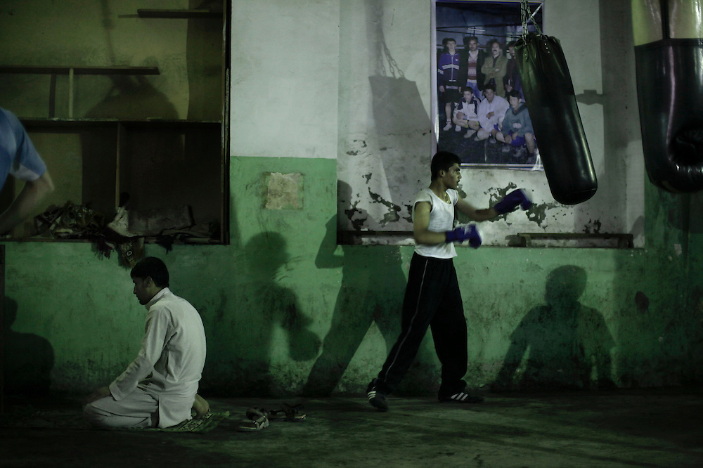 An Afghan youth (L) pauses during his training to pray as a colleague hits a punch bag during a training session at a boxing club in central Kabul on May 13, 2010. Under the Taliban regime boxing was among many sports banned. After the reinstatement of Afghanistan to Olympic competition in 2002, one athlete Basharmal Sultani took part in the boxing competition of the 2004 Athens Olympic Games. AFP PHOTO/Mauricio LIMA