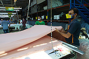 Garment workers measuring and cutting lengths of material inside an Epyllion Group garment factory in Bangladesh.
