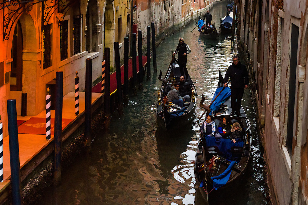 Gondolas travel underneath the Bridge of Sighs in Venice, during the early evening