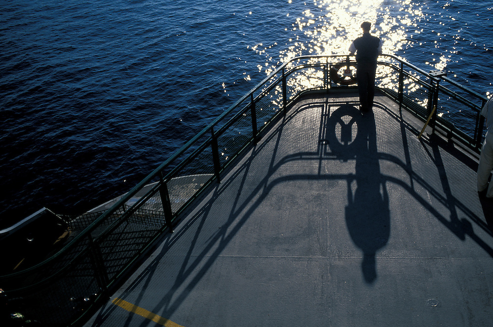 USA, Washington, Seattle, Passenger casts long shadow aboard Washington State Ferry on summer evening