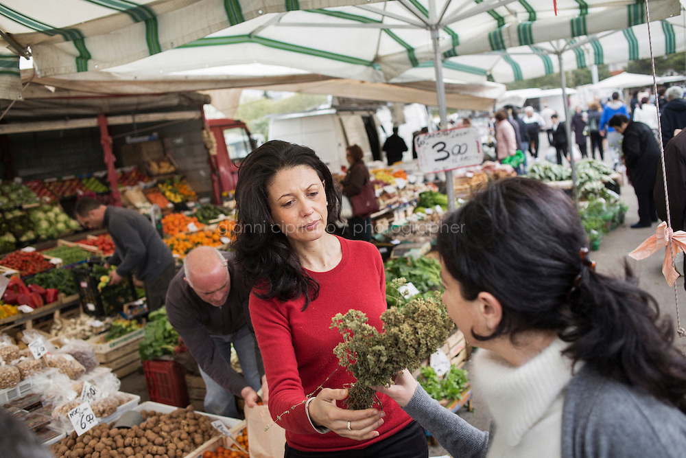 LECCE, ITALY - 4 APRIL 2014: Cinzia Rascazzo (40), founder of a Lecce cooking and food-tour outfit called Stile Mediterraneo, hands over oregano to her sister and business partner Marika (42, cardiologist) at a local market in Lecce, Italy, on April 4th 2014.<br /> <br /> Mrs Rascazzo, an extra virgin oil taster, wine sommelier and Harvard MBA who worked for Goldman Sachs in New York and London, quit investment banking several years ago to &ldquo;do something to help my region&rdquo;.&ldquo;When I was living abroad I always noticed that only Tuscany and Northern Italian regions were getting all of the attention,&rdquo; said Ms. Rascazzo. &ldquo;Nobody knew about Puglia or our way of eating, or our wines, or our producers. It was just Mafia, pizza spaghetti--the usual things associated with the south.&rdquo; Today she conducts food tours, leads visits to local producers and oversees cooking classes, where guests learn to make orecchiette, sweet-and-sour bell peppers, cakes with ricotta cheese and much besides. She is frequently joined by her sister, who draws on her medical background to impart scientific and nutritional details about the dishes. Dr. Rascazzo&rsquo;s recipes and information come together in her English ebook, &ldquo;The Cuisine of Southern Italian Women: Mediterranean Secrets for a Healthy and Happy Life.&rdquo;