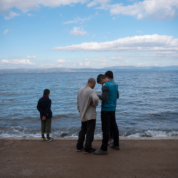 Four migrants from the Middle East, who earlier in the day had traveled by boat from the Turkish coast (background) to the Greek island of Lesbos, gather around a mobile phone. Like hundreds of thousands of others in 2015, they were transiting through the Greek islands on their way to the European mainland, where they hoped for asylum.