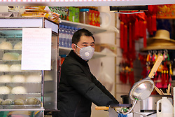 © Licensed to London News Pictures. 01/03/2020. London, UK. An Asian shopkeeper wearing a surgical face mask in a Chinese Art and Craft shop in Chinatown, as a precaution against new type coronavirus (COVID-19). Twelve more people have tested positive for coronavirus in the UK, bringing the total number of cases to 35. Photo credit: Dinendra Haria/LNP