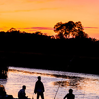 Three men fishing in a river pause to look at the brilliant sunset sky.