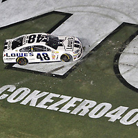 NASCAR Sprint Cup driver Jimmie Johnson (48) celebrates after winning the NASCAR Coke Zero 400 Sprint series auto race at the Daytona International Speedway on Saturday, July 6, 2013 in Daytona Beach, Florida.  (AP Photo/Alex Menendez)