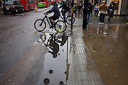 over a puddle after rainfall in Oxford Street, central London.