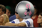 A Dallas Cowboys fan wears an oversized Cowboys helmet with a pink ribbon painted on it in honor of breast cancer awareness month during the NFL week 6 football game against the Washington Redskins on Sunday, Oct. 13, 2013 in Arlington, Texas. The Cowboys won the game 31-16. ©Paul Anthony Spinelli