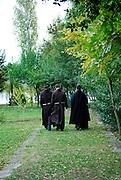 Monks waking away from camera, Krka Franciscan Monastery, island of Visovac, Krka National Park, Croatia