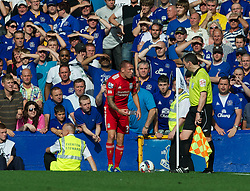 LIVERPOOL, ENGLAND - Saturday, October 1, 2011: Liverpool's Craig Bellamy shows the assistant linesman a bottle that was thrown at him from the stands by Everton supporters during the Premiership match at Goodison Park. (Pic by David Rawcliffe/Propaganda)