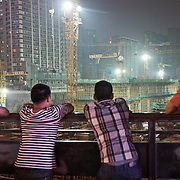 Rural residents observe a construction site in southwestern China next to tall buildings.<br /> <br /> China is pushing ahead with a dramatic, history-making plan to move 100 million rural residents into towns and cities over the next six years.<br /> <br /> Moving farmers to urban areas is touted as a way of changing China&rsquo;s economic structure, with growth based on domestic demand for products instead of exporting them.