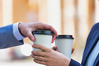 Close up photo of businesswoman giving businessman a cup of coffee