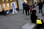 London 8/1/13: A man dressed as a NASA moon walking astronaut walks along Oxford Street outside the Selfridges department store in central London - part of a PR promo for deodorant brand Lynx who have launched a competition, with the first prize a once-in-a-lifetime chance to blast into orbit. The 22 winners, which will include one Brit, will experience Earth from outer space on the Lynx SXC (Space Expedition Corporation) space shuttle. Shoppers and passers-by seem oblivious to this symbol of 20th century American technology, now reduced to a PR stunt for the Lynx aftershave brand hosted by Selfridges. Selfridges, also known as Selfridges & Co, is a chain of high end department stores in the United Kingdom. It was founded by Harry Gordon Selfridge. The flagship store in London's Oxford Street is the second largest shop in the UK (after Harrods) and opened 15 March 1909.