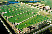 Rubber lattice keeps duckweed evenly dispersed at this low-energy sewage-treatment facility, which employs entirely natural processes.  Sewage first enters settlement ponds; wastewater is then pumped into wetland marshes, where plant and animal life absorbs nutrients.  Next, the remaining water is transferred to this pond, where duckweed filters out residual impurites.
