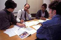 University lecturer having discussion with small group of students.