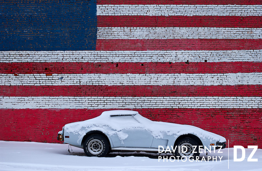 An old Corvette sits covered in snow in front of a wall painted with an American flag in Peoria, Ill., on Feb. 7, 2008.