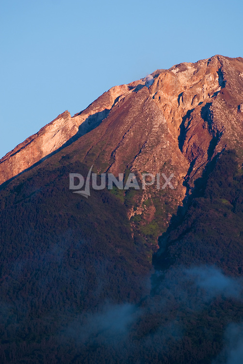 The summit of Mount Ebu Lobo, Bajawa, Flores, glows at sunset.