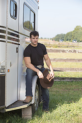 hot cowboy sitting on a horse trailer