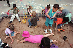 Multiracial group of nursery school children using spades to play with sand in playground sandpit,