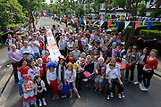 Group portrait of a neighbourhood street party in Dulwich, south London celebrating the Diamond Jubilee of Queen Elizabeth. A few months before the Olympics come to London, a multi-cultural UK is gearing up for a weekend and summer of pomp and patriotic fervour as their monarch celebrates 60 years on the throne and across Britain, flags and Union Jack bunting adorn towns and villages.