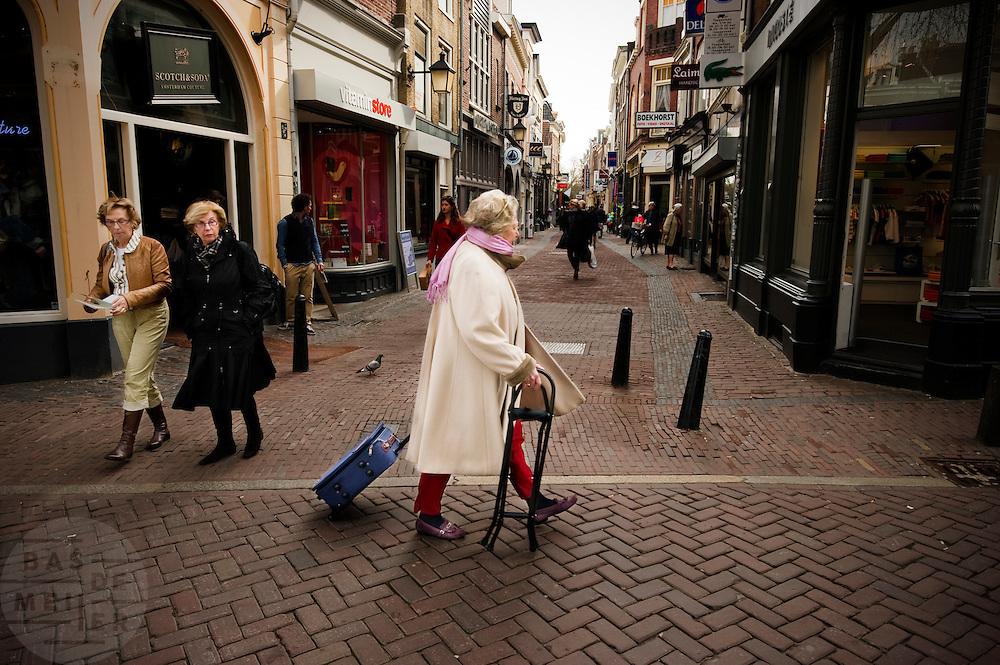 Een oudere vrouw loopt met een koffer op wieltjes en een steun door Utrecht