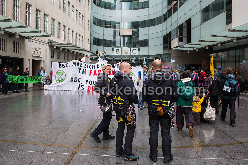 London, UK. 11 October, 2019. Specialist police officers prepare to remove climate activists from Extinction Rebellion standing on the glass parapet above the main entrance to the BBC's New Broadcasting House on the fifth day of International Rebellion protests. The activists were demanding that the broadcaster 'tell the truth' regarding the climate emergency.