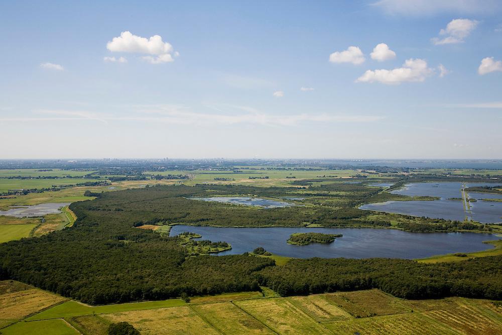 Nederland, Noord-Holland, Naarden, 14-07-2008; natuurgebied Naardermeer, oudste en een van de bekenste natuurreservaten van Nederland, bezit van de Vereniging voor Natuurmonumenten (grondlegger Jac. P. Thijsse); natuurresevaart, gezien naar AMsterdam (links de Arena, rechts van het midden IJburg / IJmeer); momenteel wordt het gebied uitsluitend doorsneden door de spoorlijn Weesp - Naarden/Bussum, er zijn echter plannen om een nieuwe weg aan te leggen vlak langs en onder het gebied,namleijk tussen het nabij gelegen Almere en Amstelveen (en door naar Schiphol) dit in verband met de fileproblematiek rond de hoofdstad; Rijkswaterstaat overweegt echter de Gaasperdammerweg te verbreden ivm die files en zo het Naardermeer te sparen; .Nature reserve Naardermeer (Naarder lake) ,  the areaa is a bird sanctuary and the oldest Dutch nature preserve; wetland, wetlands, marshland, marshlands. .luchtfoto (toeslag); aerial photo (additional fee required); .foto Siebe Swart / photo Siebe Swart