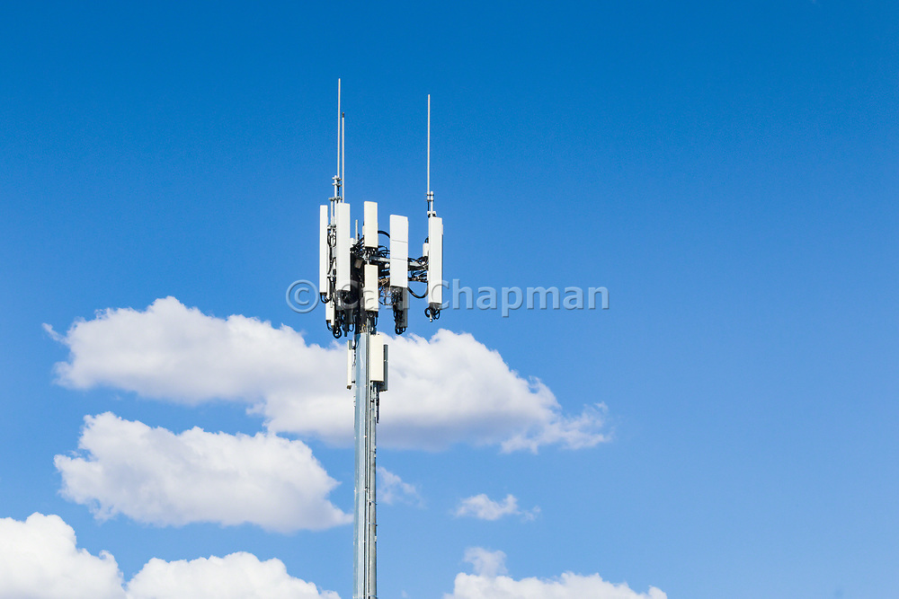 3 sector cellular telecom communications panel antenna array for the mobile telephone system on a cellsite pole tower against cumulus clouds .