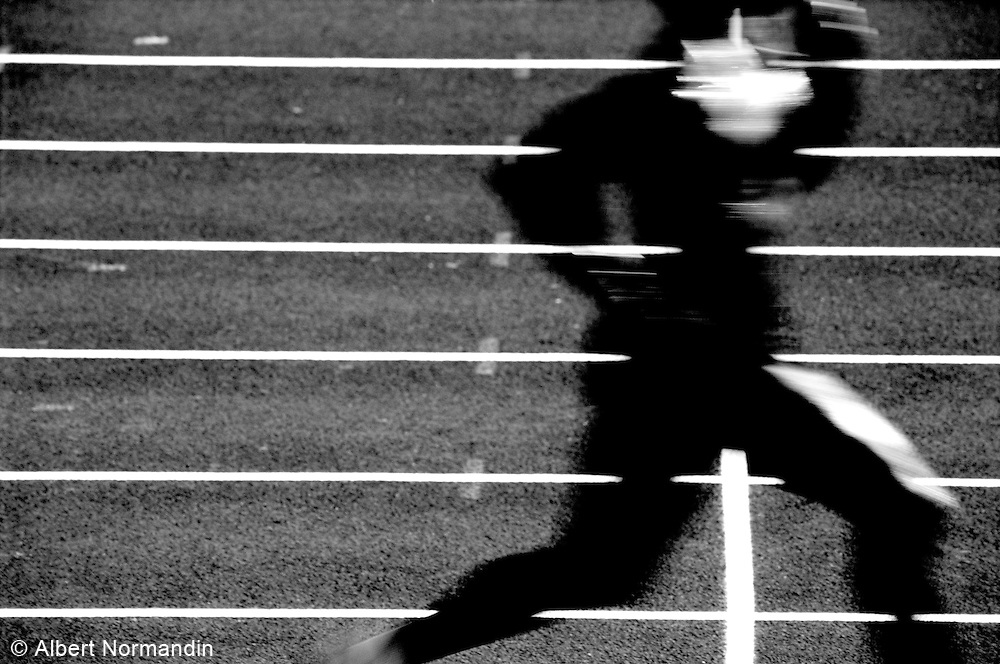 Runner blurs by on track with white lines