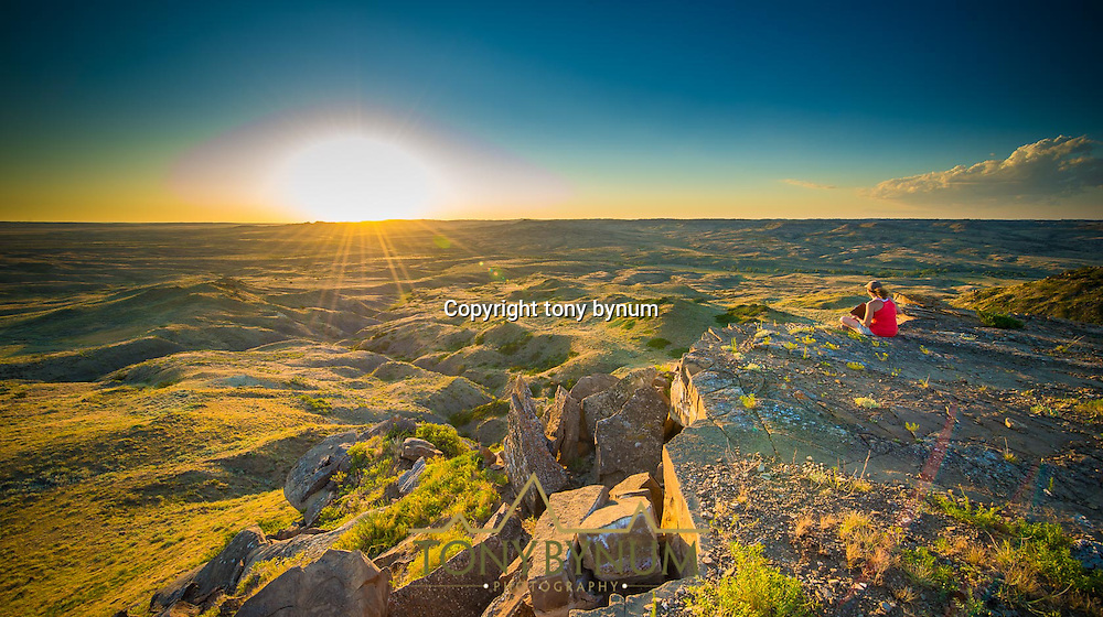 woman sitting on a rock, in eastern montana, watching the sun go down long summer evening