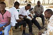 Elisha Ayibasiya (centre) marks his students books during break time. Tonga Junior High School, Ghana.