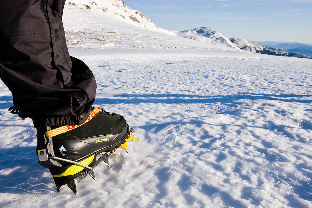 A winter hiker's crampon equipped boots on Mount Clay above the Great Gulf in New Hampshire's White Mountains.  Winter. Northern Presidential mountain range.  Gulfside Trail.